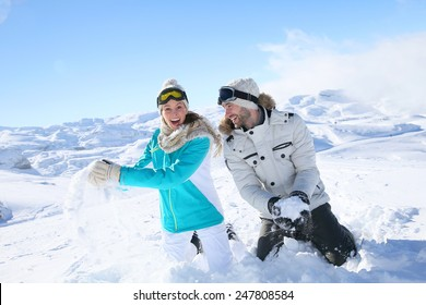 Couple in snowy mountain doing snowballs fight