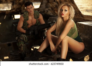 Couple of soldiers in the abandoned tank . Strong,athletic military man with weapon and sexy blonde as mate. Horizontal view.
