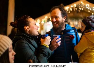 Couple and son enjoying traditional drink at Christmas market, Zagreb, Croatia.