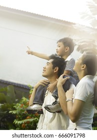 couple and son pointing at something