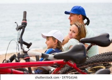 Couple with son sitting on sand with bicycles at seashore