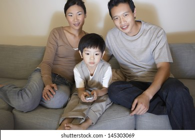 Couple with son sitting on sofa and watching television