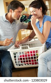 Couple Sorting Laundry In Kitchen