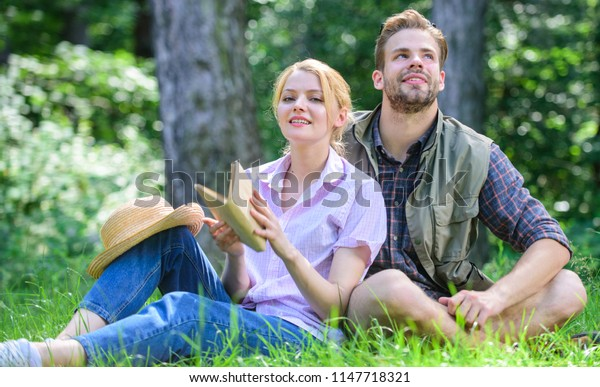 Couple soulmates at romantic date. Romantic couple students enjoy leisure with poetry nature background. Pleasant weekend. Romantic date at green meadow. Couple in love spend leisure reading book.