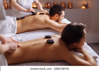 couple in spa salon having hot stone massage