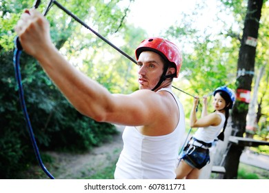 couple spend their leisure time in a ropes course. man and woman engaged in rock-climbing