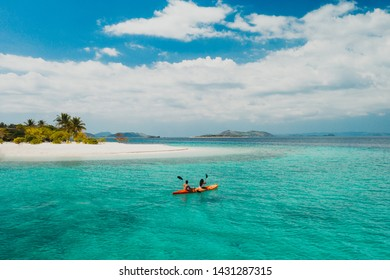 Couple spending time on a beutiful remote tropical island in the philippines. Concept about vacation and lifestyle.  kayaking and doing activities