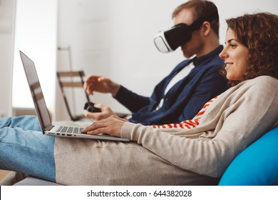 Couple spending time together with electronic devices. Man playing computer game with VR googles. Woman typing message using laptop