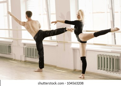 couple in sportswear stretching in aerobics room