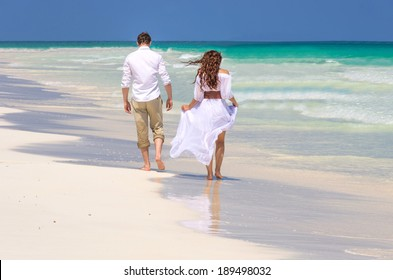 Couple of spouses walking on a tropical beach