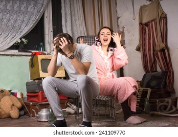 Couple in a squalid room having an argument as they sit on a wire crate with the man holding his head in his hands and the wife in her dressing gown venting her anger