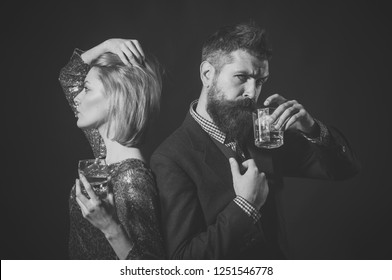 Couple stand back to back with wineglasses. Couple quarreled with strict face at corporate party. Man and woman in fancy clothes drink wiskey on dark background. Couple misunderstanding concept.