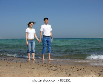 couple stand. faces. sea. sunny day