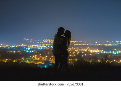 The couple stand on the background of the city lights. evening night time