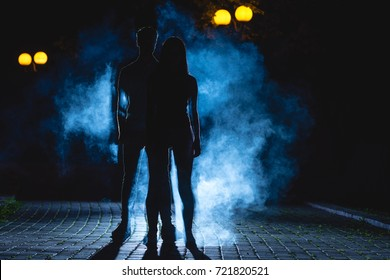The couple stand on the dark alley on the blue fume background. night time