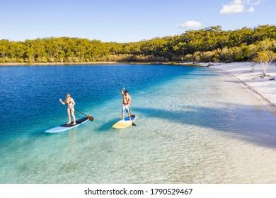 Couple stand up paddle boarding on Lake Mckenzie, Fraser Island, Queensland, Australien