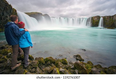 A couple stand together viewing Godafoss waterfall in Iceland.