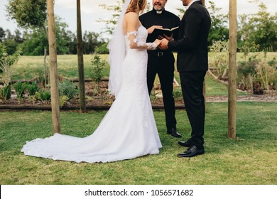 Couple standing before the priest for wedding ceremony outdoors in the park. Bride and groom standing outdoors in the presence of priest during their wedding ceremony.