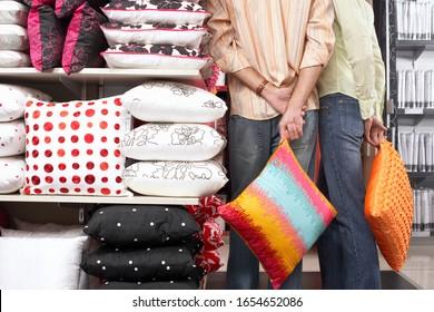 Couple standing beside shelf in shop, carrying orange cushions