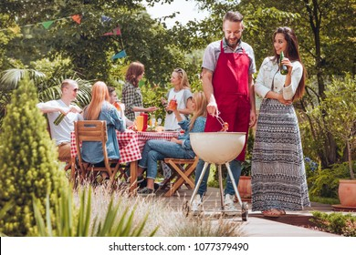 A couple standing by a grill, the man turning around a sausage, the woman with a beer bottle in her hand, with other people by a table enjoying their time during a summer barbeque in a backyard