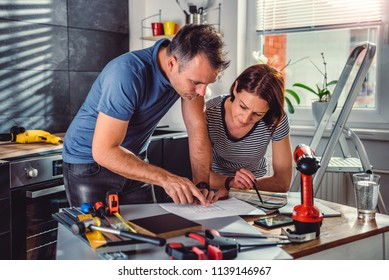 Couple standing by the table and looking at blueprints during kitchen renovation