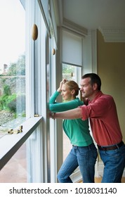 Couple standing by window together