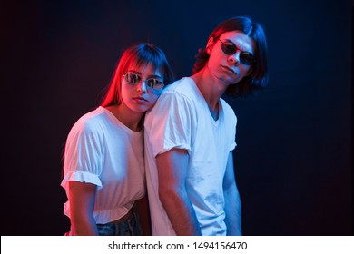 Couple standing in dark room with red and blue neon lighting.