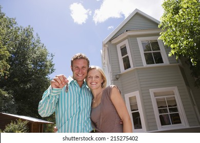 Couple standing in driveway in front of detached house, man holding aloft set of keys, smiling, portrait