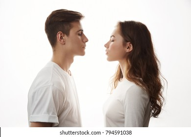 Couple standing face to face with their eyes closed. Boyfriend and girlfriend imagine their future together. There is only one mismatch. She sees cat and he is more like a dog person.