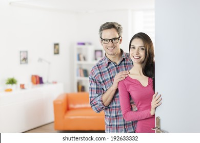 couple standing at front door to invite people at home