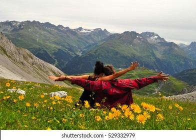 Couple standing with hands wide open in beautiful nature landscape with wild yellow flowers and snowy mountains from Austria / Freedom in nature with young couple in love