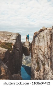 Couple standing hugging on Kjeragbolten Traveling in Kjerag mountains Norway vacations adventure lifestyle family man and woman together romantic journey