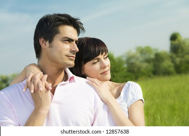 Couple standing in meadow, arm around and looking away. Copy space