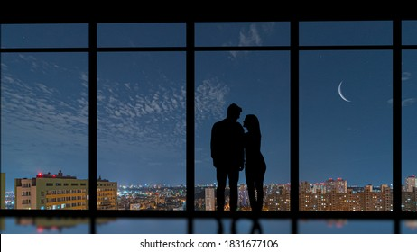 The couple standing near the panoramic window on a city moon background