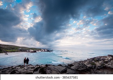A couple standing at the ocean edge of a bay with a dramatic stormy sky overhead