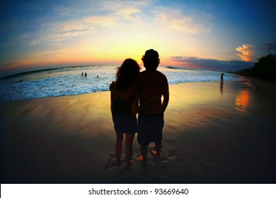 Couple Standing on Beach During Romantic Sunset with Ocean Waves and Sand