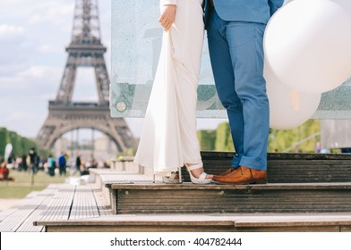Couple standing on the Champ de Mars under the Eiffel Tower in Paris, France at their wedding day