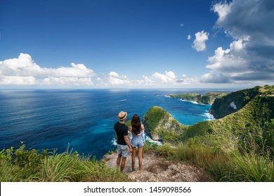 Couple standing on the clif and looking on popular place in Nusa Penida - Kelingking beach. Travelling couple