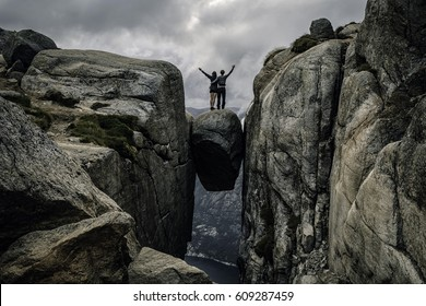 A couple is standing on the edge of a boulder (Kjeragbolten) stuck in between the mountain crevices of Kjerag above a fjord, near Lysebotn, Rogaland, Norway.