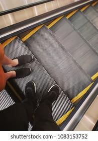 couple standing on escalator