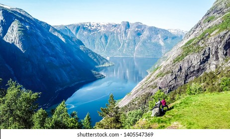 A couple standing on the meadow with a majestic view on Eidfjord from Kjeasen, Norway. Slopes of the mountains are overgrown with lush green grass. Water has dark blue color. Sunny and clear day