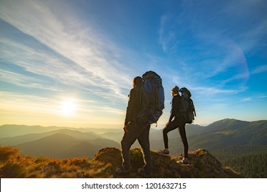 The couple standing on the mountain with a picturesque sunset background