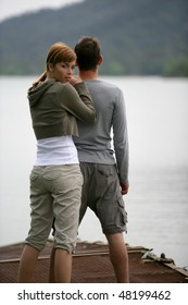 Couple standing on a pontoon by a lake