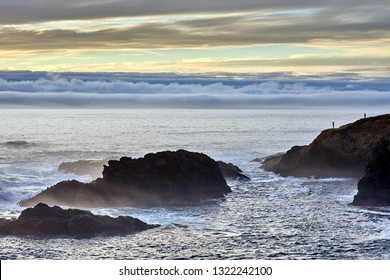 A couple standing on a rocky point by the ocean looking across the water to a beautiful cloud-filled sunset as waves crash into the shore in Mendocino on California's Pacific coast