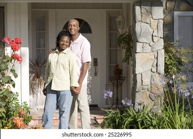 Couple Standing Outside Their House