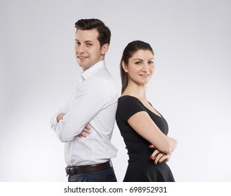A couple standing and posing back to back