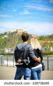 A couple standing in the Rheinanlagen Koblenz looking to toe fortress Ehrenbreitstein.