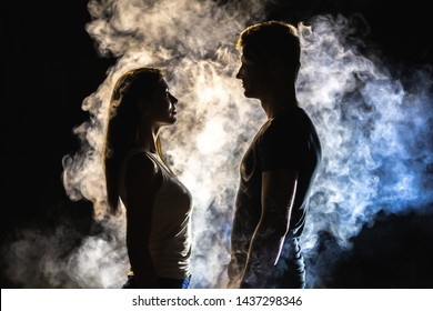 The couple standing in smoke on the dark background