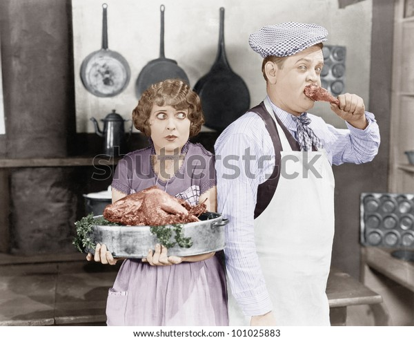 Couple standing together in a kitchen with a cooked turkey