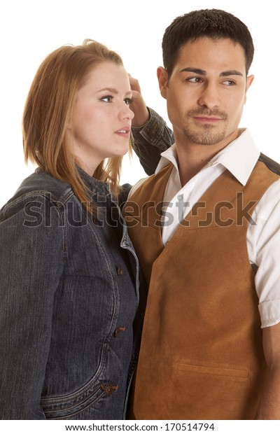 A couple is standing together and are looking to the side.